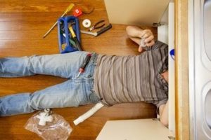 man lying on the floor doing plumbing work under the sink