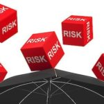 red cubes with risk written on them falling on black umbrella